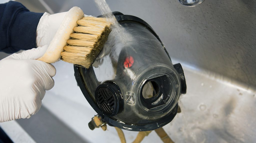 A firefighter cleans an SCBA mask.