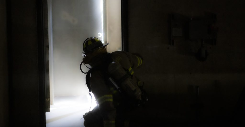 A firefighter in a smoke-filled room looks towards light streaming through a doorway.