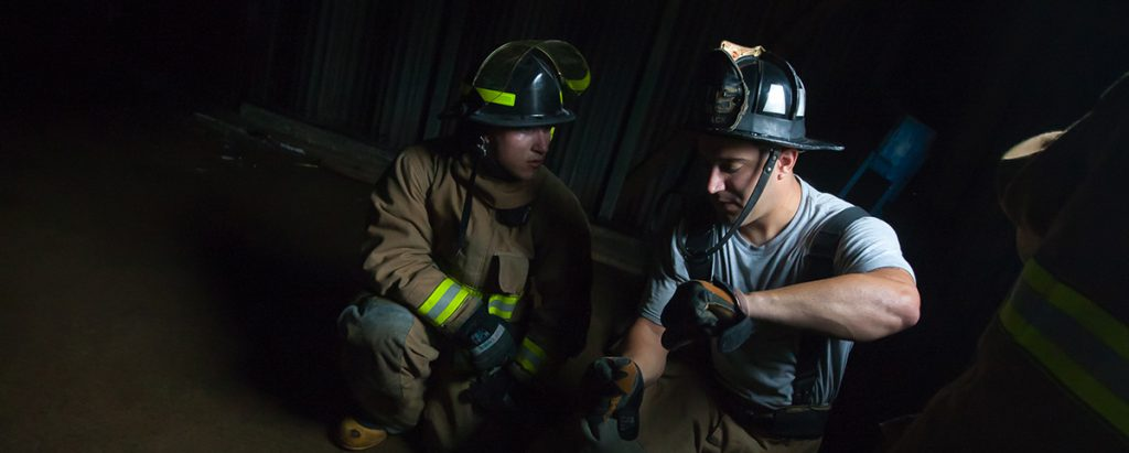 A New Hampshire fire academy recruit listens to an instructor during a break in drillyard training.